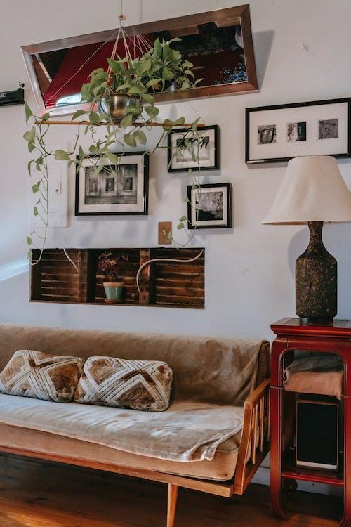Kanapa I Mała Witryna Z Elegancką Lampką Przy ścianie Ozdobiona W Domu Oprawionymi Obrazami