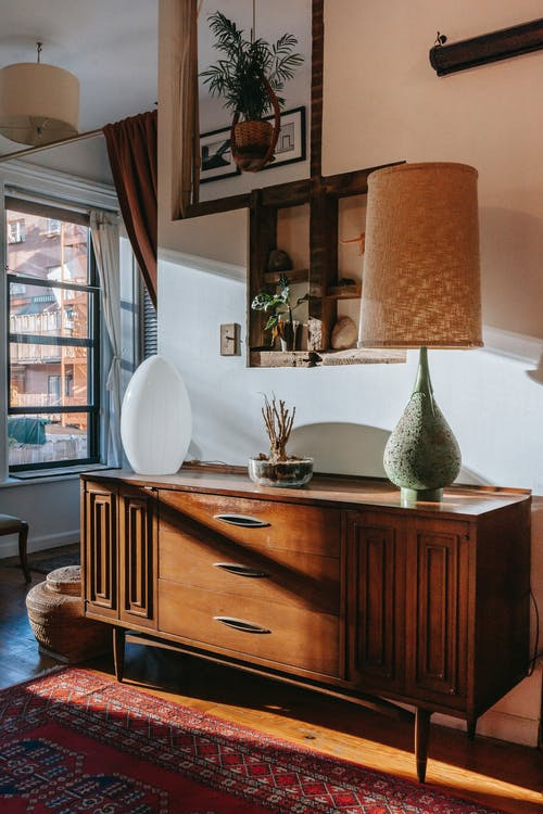 Vintage wooden cabinet on parquet floor with carpet decorated with stylish lamps and plants in spacious room in daylight