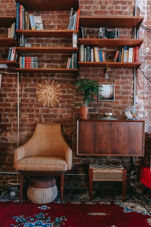 Stack of books placed on shelves attached to brick wall in cozy room with classic wooden furniture and comfortable armchair