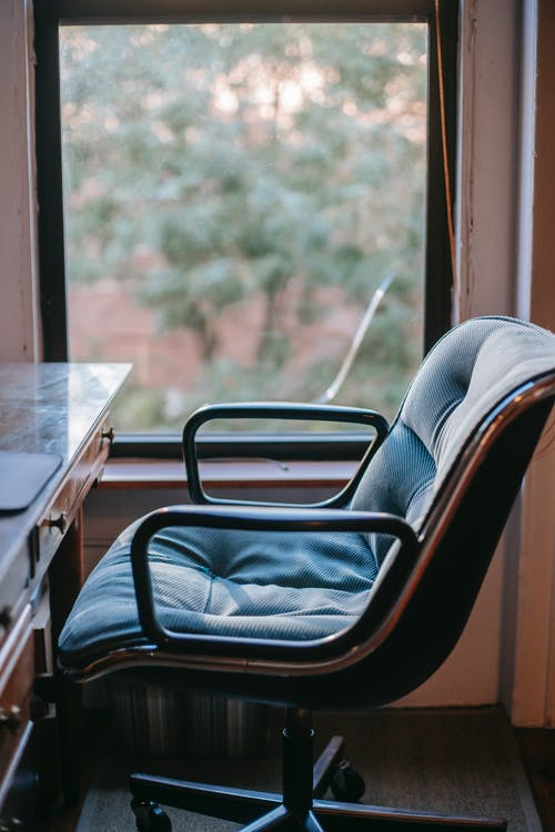 Comfy soft armchair and classic styled wooden table placed near window in cozy workspace