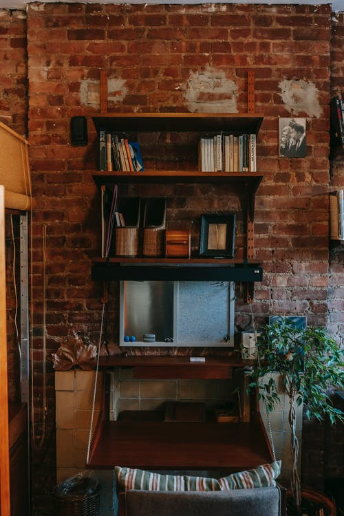 Weathered brick wall with classic shelves with books and stationery