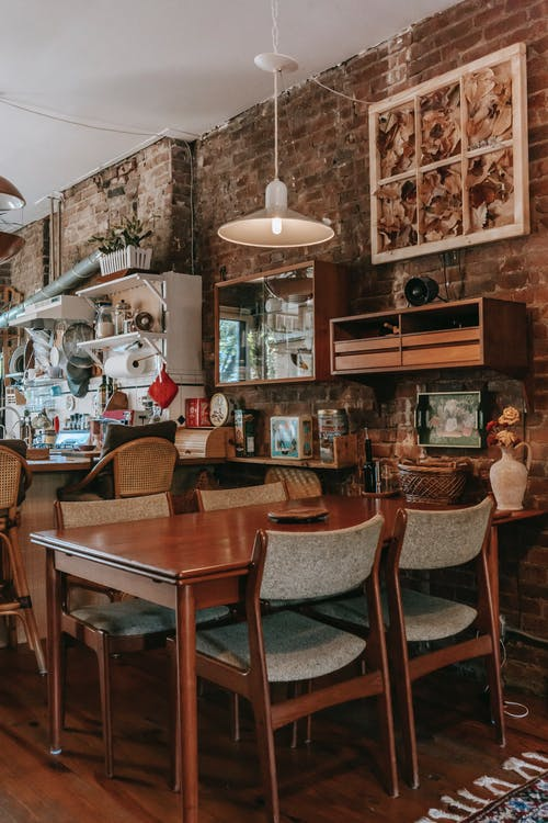 Vintage styled kitchen with classic wooden furniture and weathered brick wall