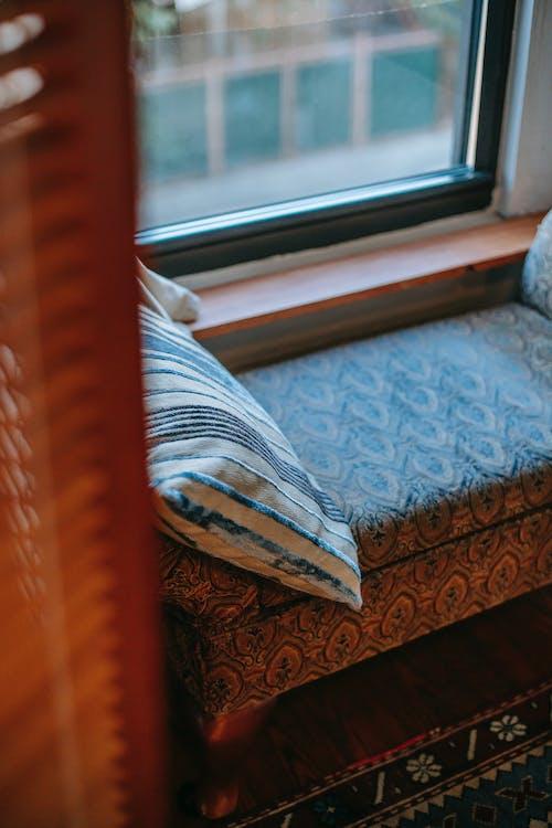 Soft pouffe with cushion near window and rug