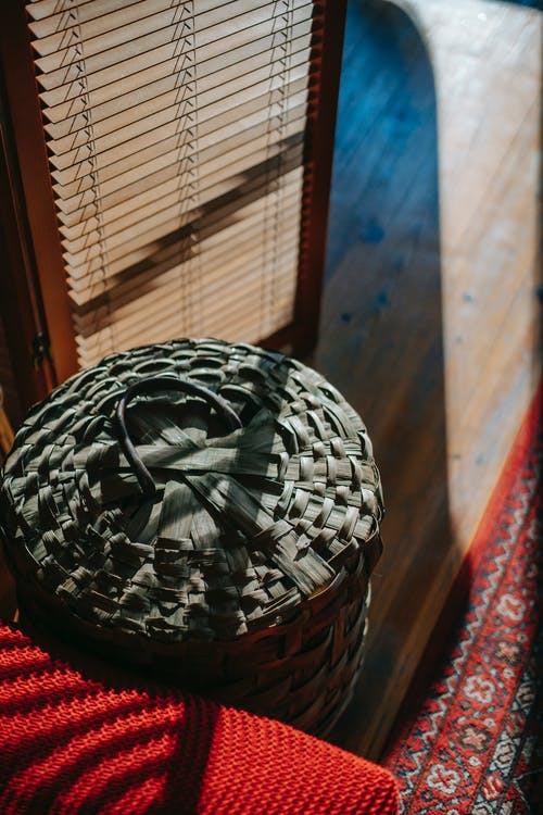 From above of decorative wicker basket with lid placed on floor near red carpet and folding screen in cozy room