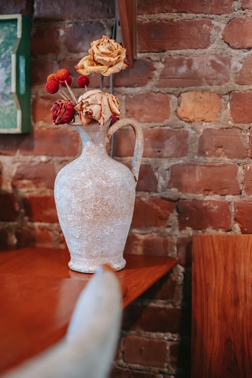 Vintage light vase with dried roses placed on wooden table near brick wall