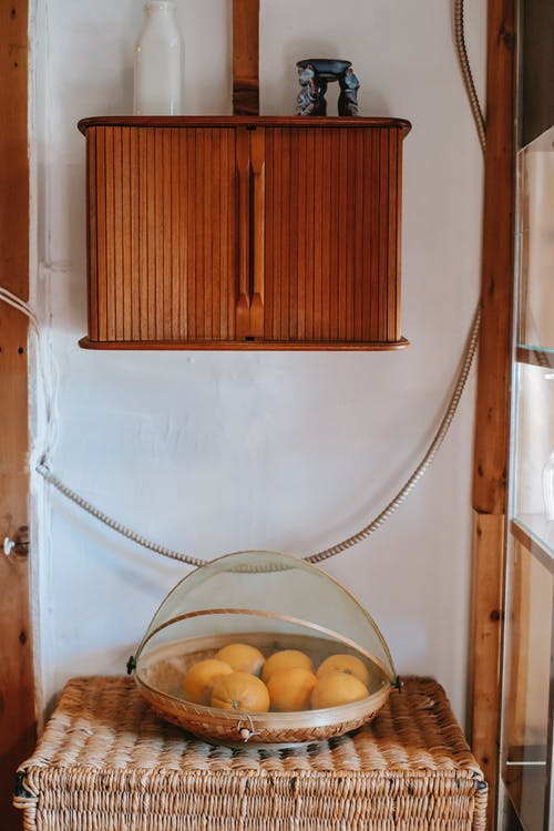 Part of vintage interior with wicker boxes and platter with oranges