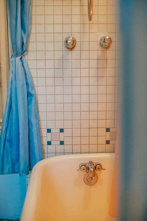 Interior of cozy bathroom with retro bathtub and shower on tile wall at cozy home