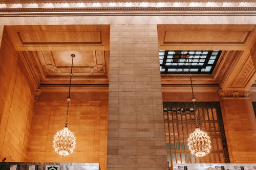 Low angle of interior of Grand Central Terminal building with brick walls and columns near classic chandeliers