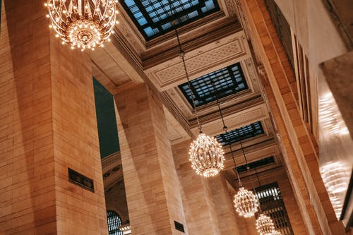 From below of classic interior of Grand Central Terminal with majestic chandeliers under ornamental ceiling with lattice over windows