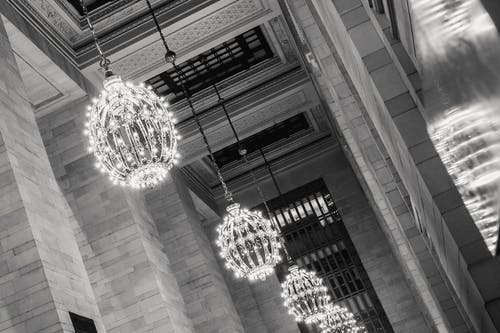Black and white of classic interior of Grand Central Terminal with majestic chandeliers under ornamental ceiling with windows