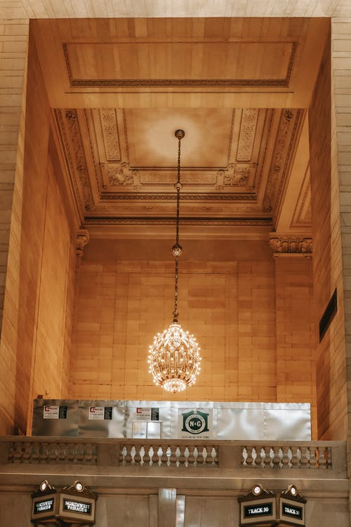From below of majestic chandelier on ornamental ceiling over balcony with stone fence in Grand Central Terminal