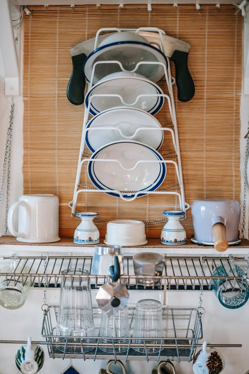 Interior of kitchen with ceramic dishes and glass on metal shelves at home