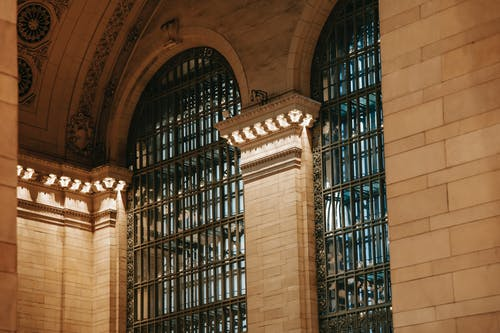 From below of illuminated interior of Grand Central Terminal station with high decorated ceiling and big windows with pillars in New York USA