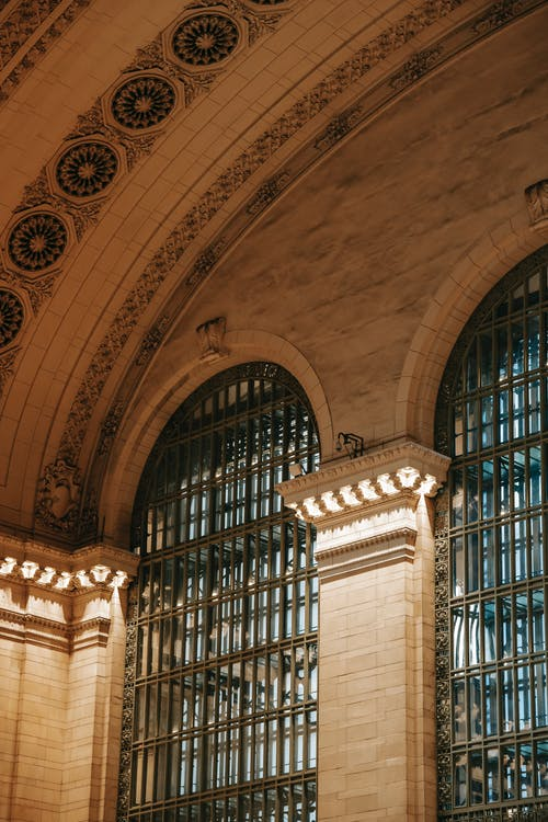 From below of ornamental ceiling of Grand Central Terminal over window with metal lattice in classic structure