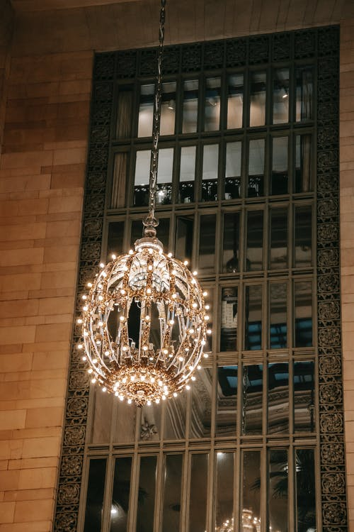 Low angle of elegant chandelier near glass window under lattice in brick building of Grand Central Terminal