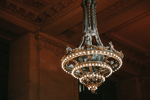 From below of classic chandelier with bright shiny lamps in old public structure