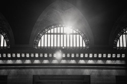 Ornamental arched window in historic building in sun rays