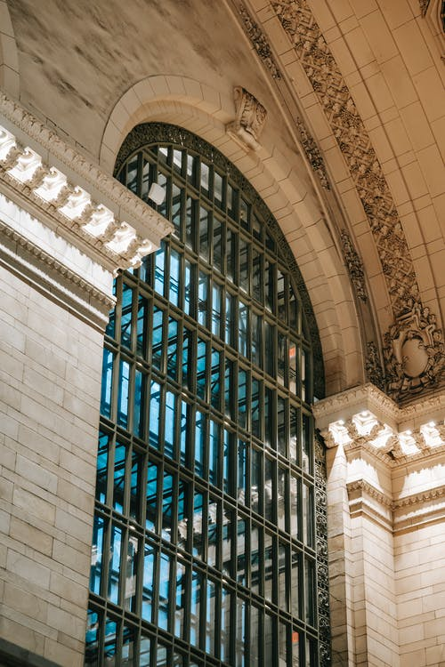 From below of Grand Central Terminal brick building exterior wall and high window with latticed glass under ornamental arch