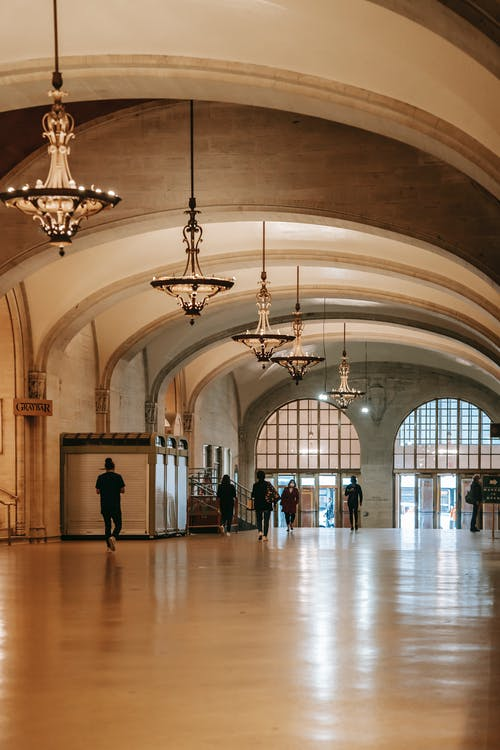 Perspective view of spacious arched corridor decorated with glass chandeliers leading to entrance doors with people walking