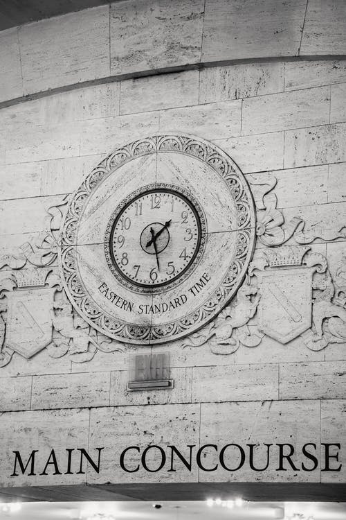 Engraving of emblem with clock on stone wall