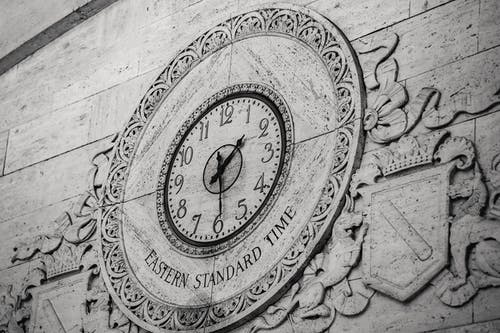 From below black and white of stone wall with ornamental details around clock showing Eastern Standard Time