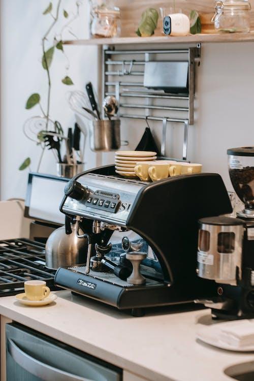 Coffee machine near stove in kitchen