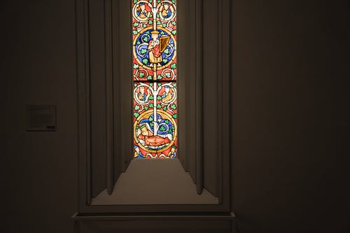 Narrow window with multicolored ornamental leaded glass in stucco frame located in dark grand cathedral