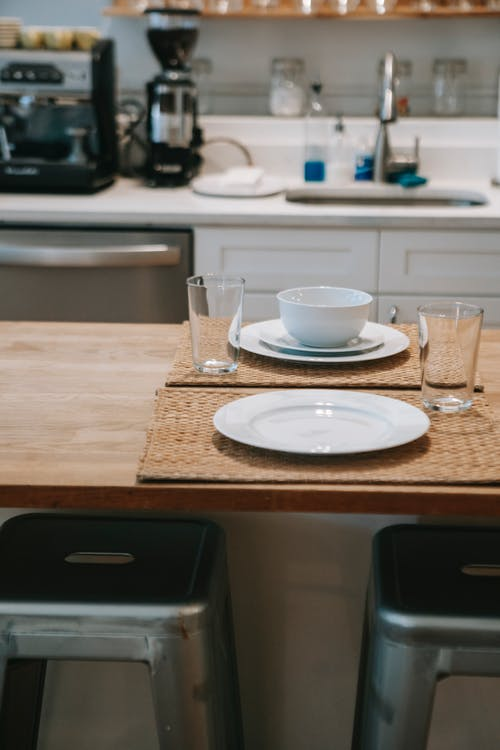 Dining table with dinnerware placed in light modern kitchen against kitchen unit with sink and appliances