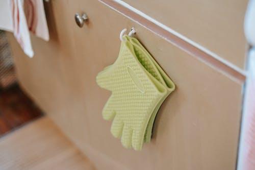 Pair of oven gloves on cabinet door in kitchen