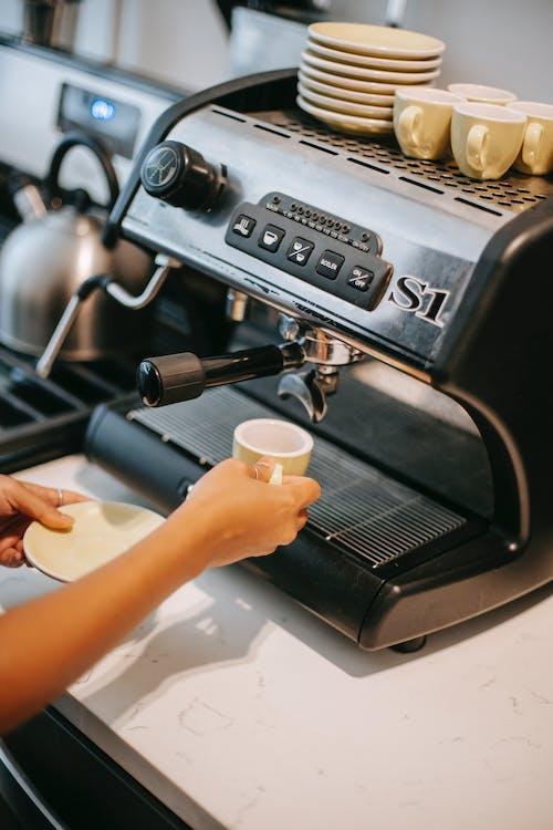 Person with ceramic cup preparing coffee in machine