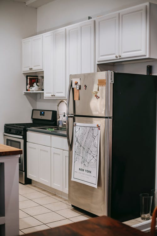 Modern light kitchen furnished with refrigerator and white cupboards placed near stove oven in modern cozy apartment with tiled floor