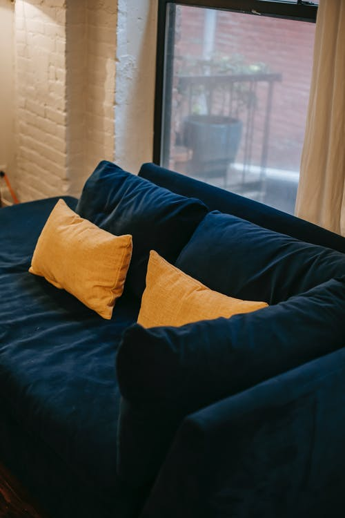 From above of blue soft couch with yellow cushions placed near window and white brick wall in light modern apartment
