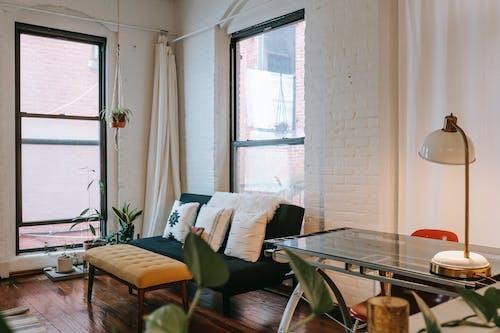 Comfortable sofa near brick wall