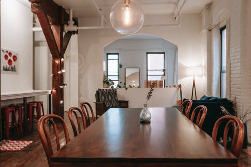 Wooden table with chairs placed in cozy room with white brick wall and garland on beam