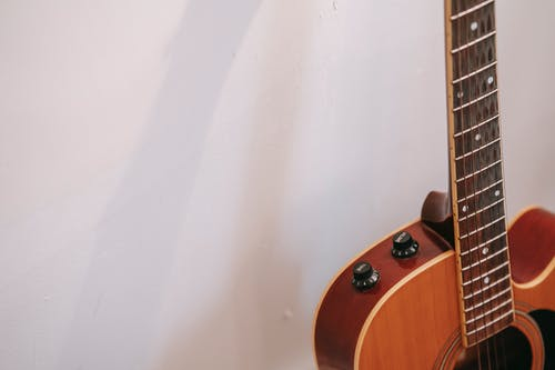 Detail of guitar neck with volume and tone knobs on body of brown musical instrument placed near white wall with shadow