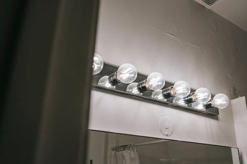 Shiny light bulbs on wall in bathroom