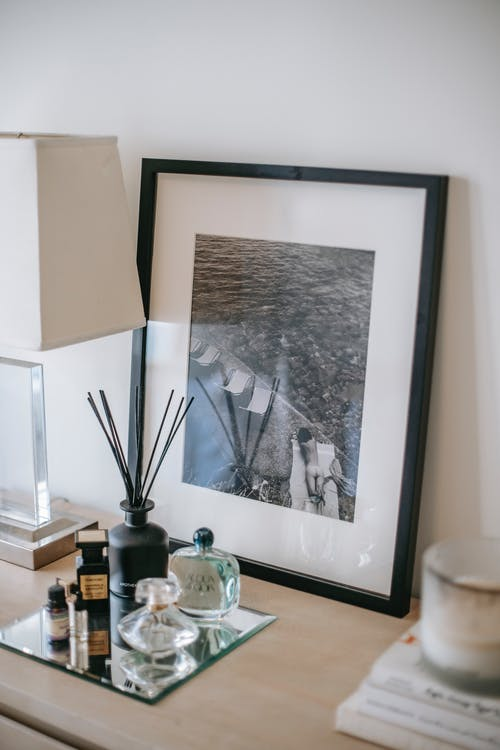 Photography in frame near perfume bottles and incense sticks with lamp near wall at home