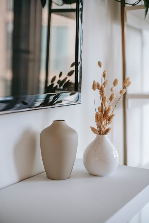 Ceramic vase with dried plant stems reflecting in mirror in house room in daytime