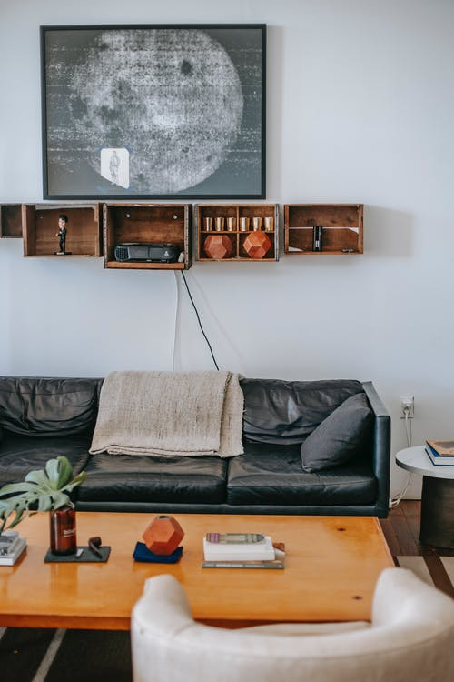 Comfortable black leather couch located under wooden bookshelves and contemporary painting on white wall and near table with white armchair in living room