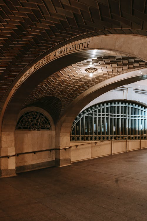 Interior of aged spacious arched passage decorated with geometric ornament leading to  subway shuttle in New York USA
