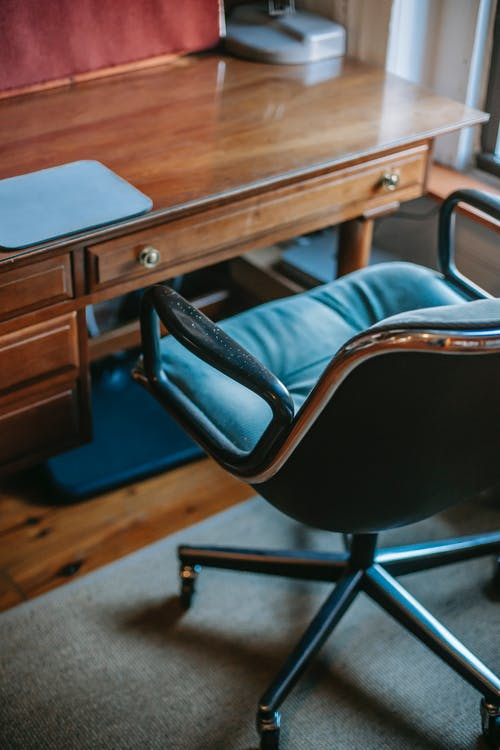 Interior of comfortable home office with retro wooden table with graphic pen tablet and black leather chair located near window in daylight