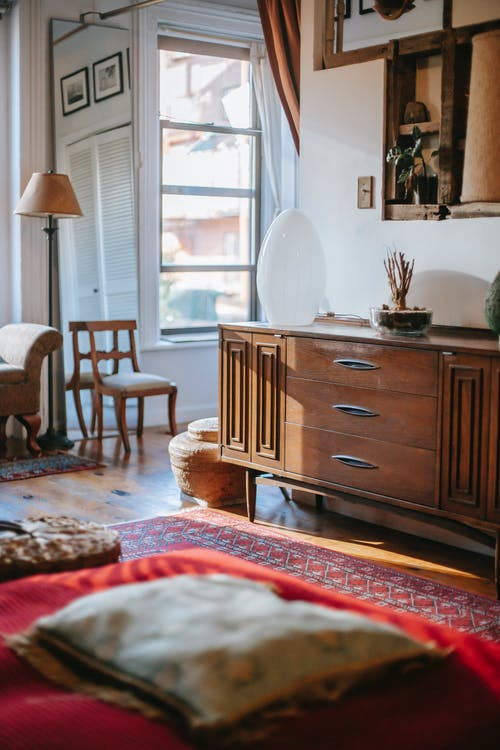 Old fashioned dresser near white wall in cozy bedroom