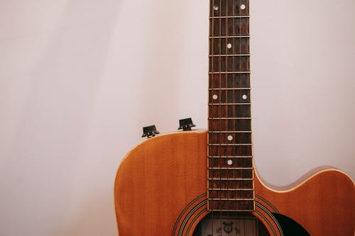Neck of acoustic guitar on white background