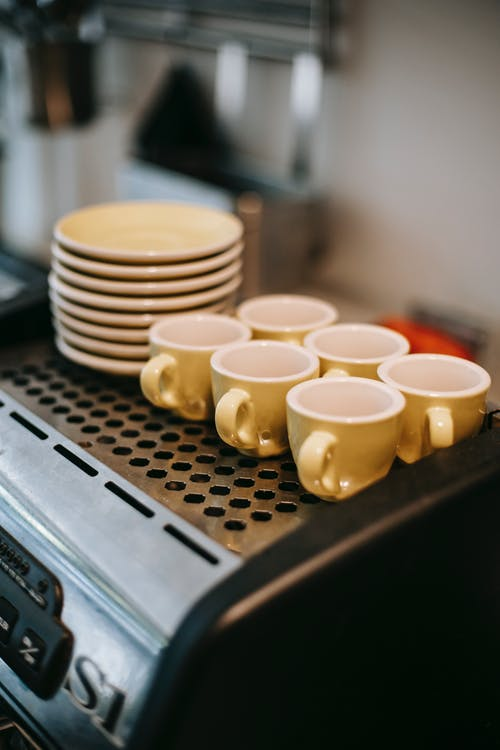 Set of colorful coffee cups and saucers standing on coffee machine in kitchen
