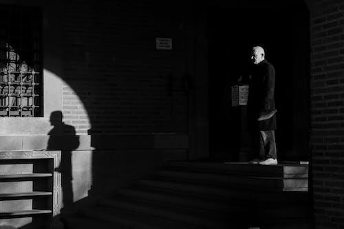 Elderly man standing on stairs near building