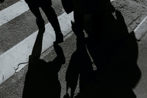 From above black and white of crop anonymous people walking on roadway with crosswalk and shadows in city