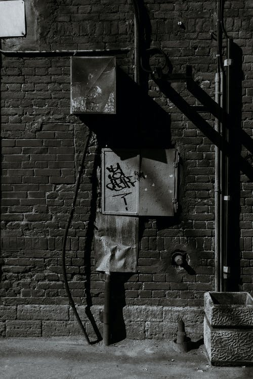 Black and white facade of brick building with metal tube and panels with graffiti