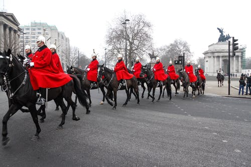 People in Red and White Uniform Riding Horses on Road