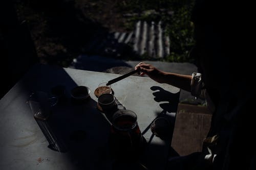 From above of crop unrecognizable person brewing hot aromatic tea into cups during ceremony on terrace at dawn