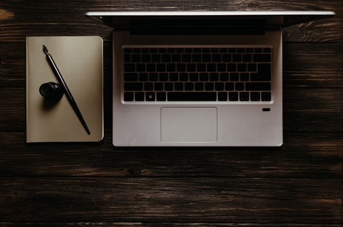 A Laptop Beside a Notebook on a Wooden Surface